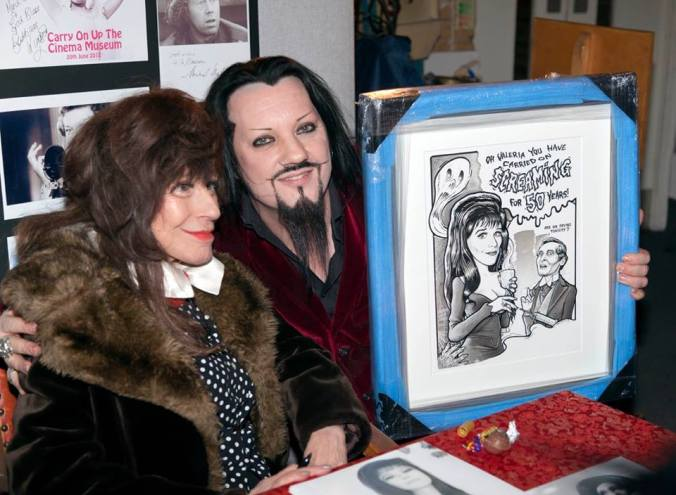 Fenella being presented with a painting to celebrate 50 years of Carry On Screaming by a fan