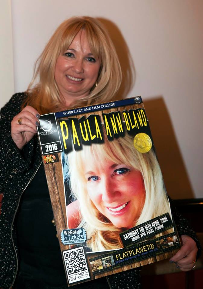 Paula Ann Bland with the poster designed for her gig by Ronnie Clark